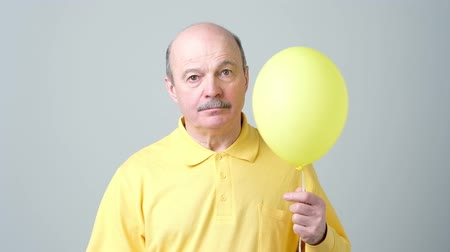 A sad senior man in a yellow shirt is holding a small balloon in his hands. Стоковые видеозаписи