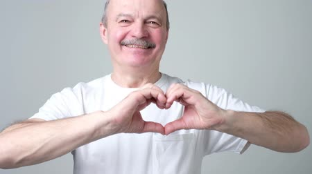 Senior man making heart figure love sign with fingerssmiling looking at camera.
