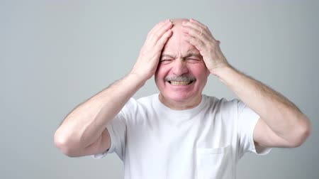 Mature man in white tshirt with closed eyes touching his head in pain.