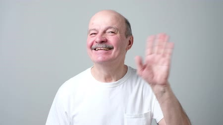 European pensioner waives hand in hello gesture while smiling cheerfully. Stok Video