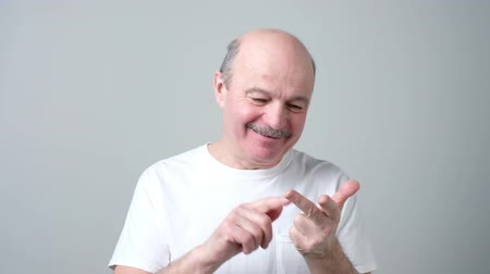 Handsome mature man counting tfrom one to five bending fingers