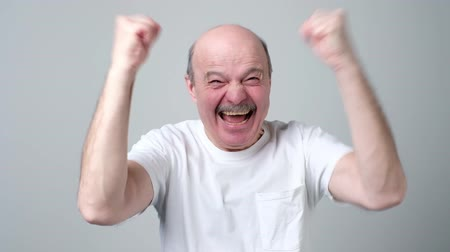 Happy bald senior man celebrating his success over gray background. Стоковые видеозаписи