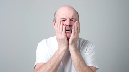 facepalm : Senior man slaps himself a couple of times trying to wake up.