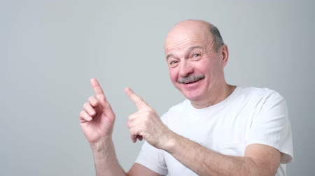 Senior man in white t-shirt pointing with index finger to important information