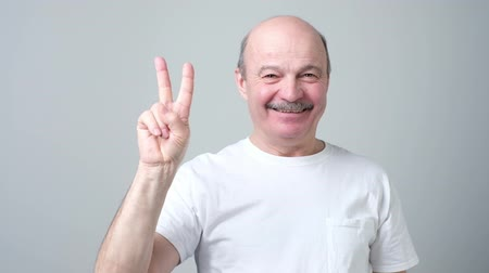 пенсионер : Senior man raising two fingers up on hand showing peace or victory symbol. Стоковые видеозаписи