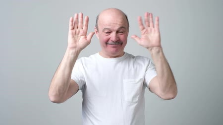Senior bald man saying bye to his friends waving his hands.