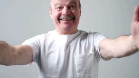 Senior man in white t-shirt, pulling hands towards camera, smiling broadly.
