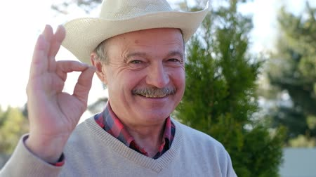 Mature man in hat smiling, doing ok sign with hand Стоковые видеозаписи