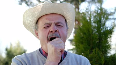 Senior man in hat yawning standing outdoor.
