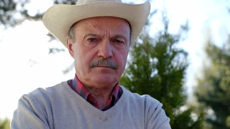unhappy old spanish man in hat frowning his face