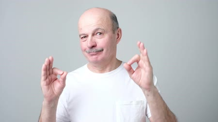 Satisfied positive man gesturing ok sign Стоковые видеозаписи