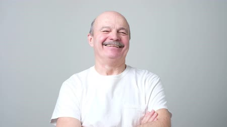 Handsome senior man in white t-shirt laughing