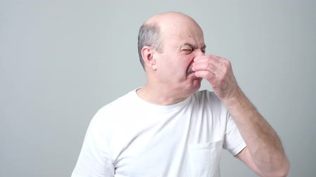 unpleasant smell : Senior spanish man with disgust on his face, pinching his nose