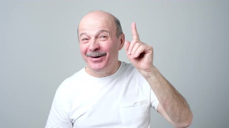Satisfied mature man showing index finger up, giving advice