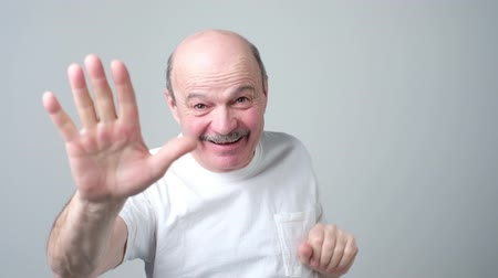 Mature man in white t-shirt shows five fingers.