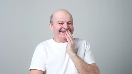 Mature bald man covering mouth and laughing.
