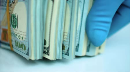 feixes : Hand in blue glove leafs through stack of US dollars. Close up view Stock Footage