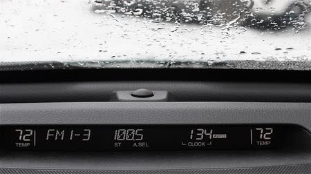 autoradio : Automotive display: radio frequency, volume, and temperature. Background snow-covered winter roads of the city. On car windshield snow falls. The windscreen wipers operate.