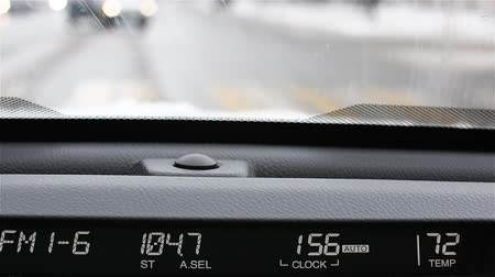 yıkayıcı : Automotive display: radio frequency, volume, and temperature. Background snow-covered winter roads of the city. On car windshield snow falls. The windscreen wipers operate.