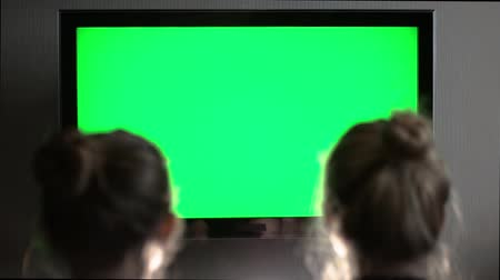 television set : Two young long-haired blond looking at green screen TV in evening home interior. Stock Footage