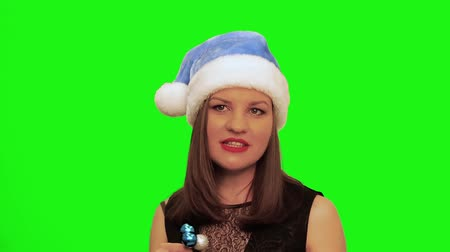 színésznő : Attractive woman in santa hat laughs, sings xmas song and dances against green screen of chromakey