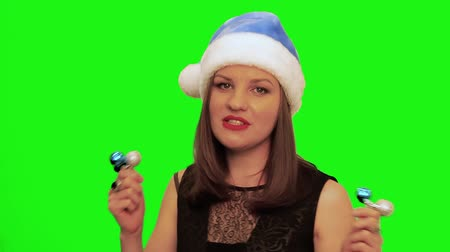 színésznő : Attractive woman in santa hat dances and sings xmas song against green screen of chromakey Stock mozgókép