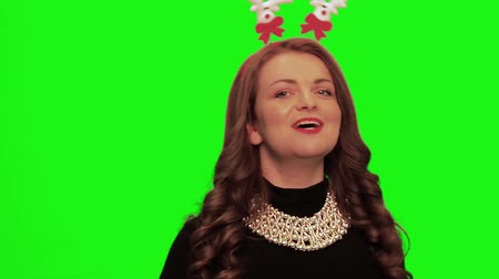 színésznő : Woman with curly hair wearing nice dress, christmas stuff and necklace sings and smiles against chromakey.