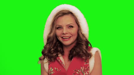 színésznő : Pretty woman with curly hair wearing christmas costume and hood looks aside laughs, sings and talks playing timbrel against chromakey. Stock mozgókép