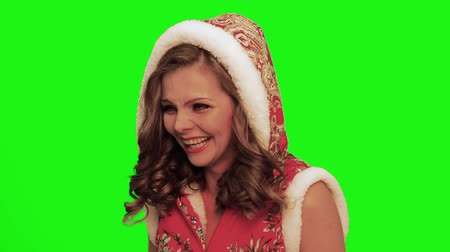 караоке : Pretty woman with curly hair wearing christmas costume and hood looks aside laughs tears against chromakey.