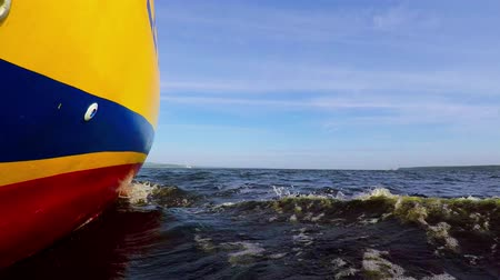 popa : Yacht with yellow body sails down river. Camera set at board bottom close to water