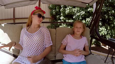 children only : Two sisters talk on the swings in the summer