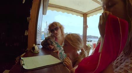 три человека : Mom and two daughters choose breakfast at beach cafe