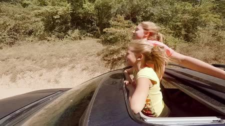 fish eye : Two happy young blondes laughing leaping out of hatch of the car on the move against the forest