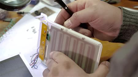 patron : White man repairing a broken electronic led lamp in old workshop Stock Footage