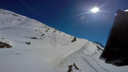 hegyoldalban : View from top to bottom on snow-covered ski slope and traces from the chair lift. First-person view