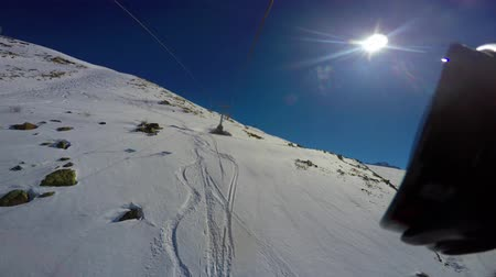 View from top to bottom on snow-covered ski slope and traces from the chair lift. First-person view