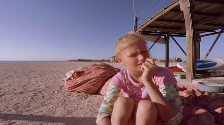 camera move : Little girl emotionally tells something on the beach