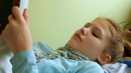 Girl with a scarf on neck reads in bed wiating for doctor