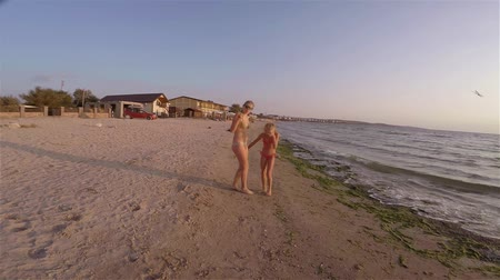 Two sisters of the blonde in a bathing suit are funny dancing on the beach Stock Footage
