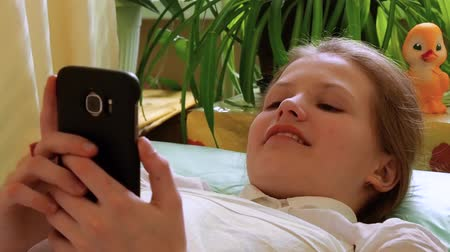Little girl looks at smartphone lying on couch in hospital Stock Footage