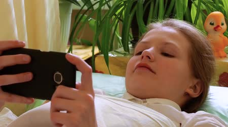Girl covered with blanket watches video on smartphone lying on couch in hospital.
