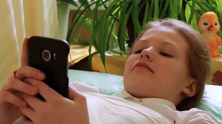 elsődleges : Little girl uses smartphone and laughs, looks away lying on couch in hospital Stock mozgókép