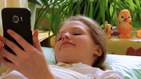 Girl looks away and at smartphone lying on couch in hospital,