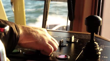 kaptan : Tug master controls deck winch. Close-up of hands in a day light