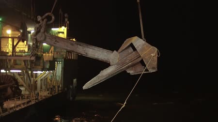 baltské moře : Crane carries an enormous anchor from the boat to the platform in the night