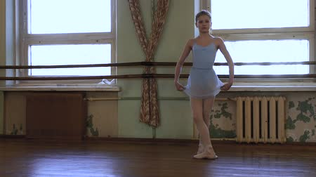 тапки : Girl in blue leotard and blue ballet skirt holds skirt in hands and does battement tandu during choreography class in frayed classroom.