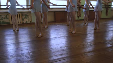 pirouette : Legs of girls standing in third position during ballet lesson in frayed classroom. Stock Footage