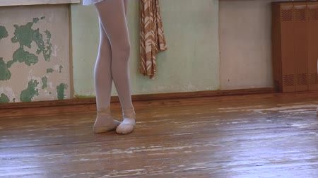 тапки : Girl stands in third position near frayed wall during ballet class. Стоковые видеозаписи