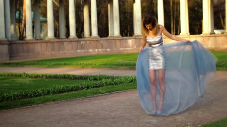 trimmelés : Beautiful model in high heeled shoes, silver and blue dress handles dress and walks preparing to pose outdoors with columns on background.