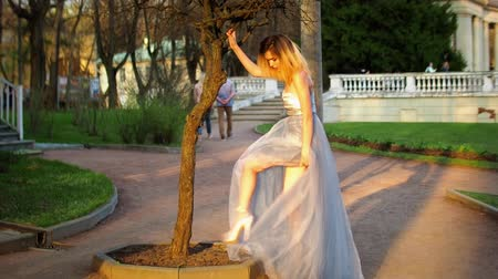 professional photography : Beautiful skinny girl in silver and blue dress poses adjusting dress during photo session in antique estate.